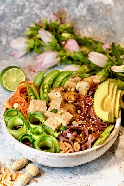 this is a bowl of tofu with brown rice noodles, avocado, and cucumber slices