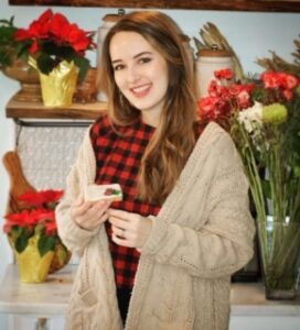 Lauren is standing in her kitchen around the holidays. She is holding a vegan cookie, wearing a red checkered shirt and beige sweater surrounded by pointsettias.