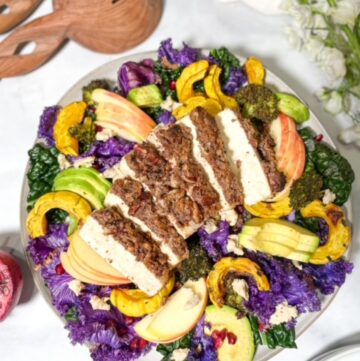 crispy pecan crusted tofu atop a bed of purple kale, delicata squash, roasted broccoli, and avocado